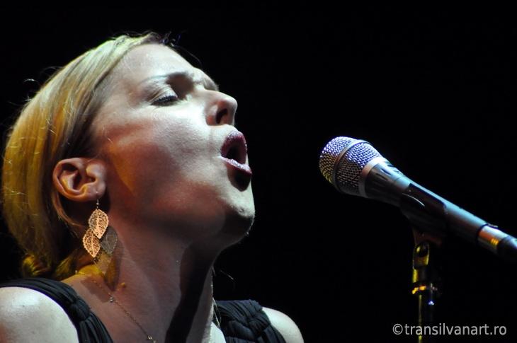 Blonde woman singing in microphone