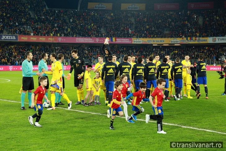 Soccer players of Spain and Romania enter the field